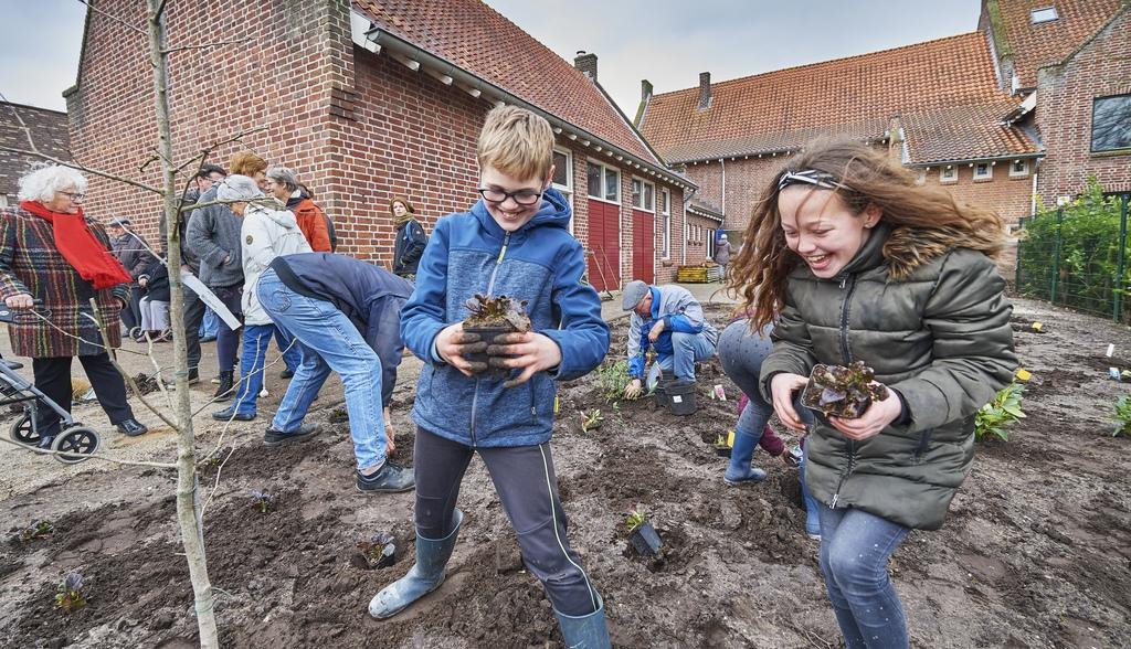 Timo Hol en Jill Verbruggen van Den Dijk helpen bij het vol planten van de beleeftuin. Foto VAn Assendelft