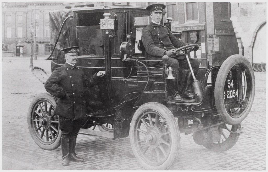 → De heer H.F. Koek achter het stuur van een elektrische Atax, op de hoek van het Damrak. De foto stamt uit 1910. foto stadsarchief