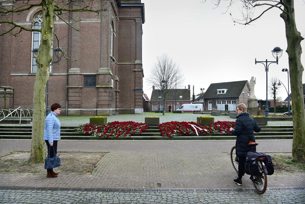 De inwoners van het Brabantse Erp hebben op de trappen van de Sint-Servatiuskerk meer dan duizend rode rozen gelegd. Het dorp is met zeven doden zwaar getroffen. Foto Marcel van den Bergh / de Volkskrant